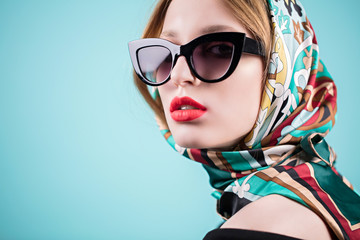 Fashionable portrait of a stylish young woman in sunglasses, isolated on blue background