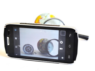 compass, globe of Earth and magnifier glass through camera mobile phone on white background