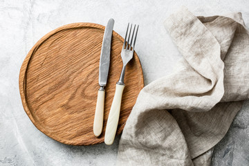 Rustic table setting with vintage silverware, wooden board and textile. Top view, copy space for text