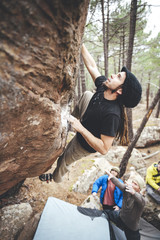 Rock climber with dreadlocks climbing overhanging boulder