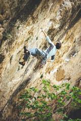 Rock climber climbing orange limestone wall reaching across for handhold on rock face