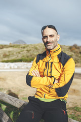 Portrait of mountaineer seated over  a wooden fence looking at horizon