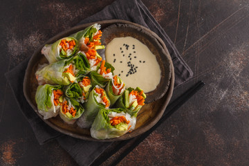 Fresh handmade vegan asian spring rolls with rice noodles, avocado, carrots and tahini dressing on black dish, dark background. Top view, copy space.