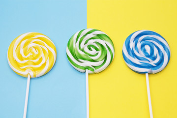 spiral colored round lollipops on yellow and blue background