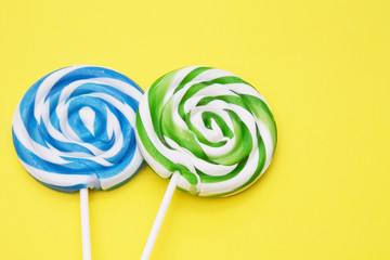 spiral colored round lollipops on yellow background