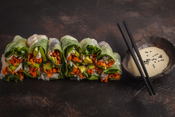 Fresh handmade vegan asian spring rolls with rice noodles, avocado, carrots and tahini dressing on dark background, copy space.
