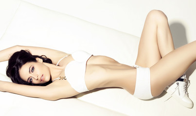 Woman in white underwear. Young, beautiful and seductive fashion model posing in swimsuit.