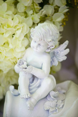 The figurine of a little angel among the decorations on the occasion or holiday.