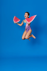 Beach Summer Vacation concept.Young girl jumping up fun on bright blue background as water sea.Cheerful child holding piece of watermelon.Energy caucasian teenage dressed in swimsuit for swimming.