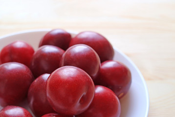 Ripe Gulf Ruby Plum Fruits Piled up on White Plate Served on Wooden Table