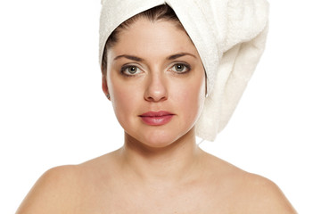 Young beautiful woman with towel on hr head on white background