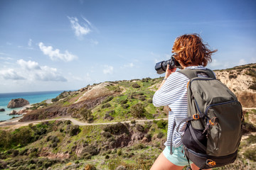 young woman traveler with a camera in the hands of a background of stunning scenery, travel, hiking, unity with nature, freedom and vacations concept