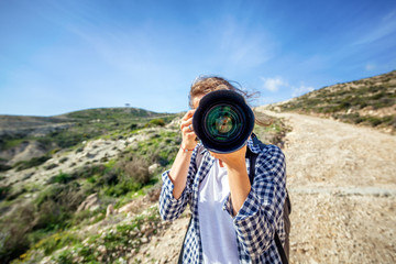 Girl traveler with a camera in hand, against a beautiful summer landscape, a lens on a viewer, travel, a blogger, summer vacation, freedom, hiking concept