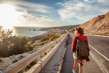 A young woman traveler walks along a highway, against the background of a sunset and sea coast. Travel and freedom, adventures and directions for travel