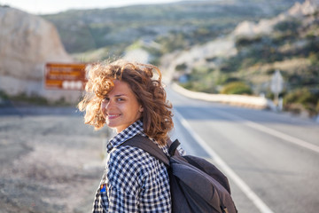 Portrait of a beautiful young woman with fluttering hair walking on the road in the setting sun