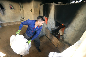A worker throws a sesame bag in the stove at the sesame factory in Dohuk