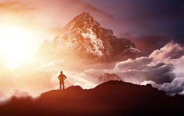 Man standing on a mountain enjoying the sunrise