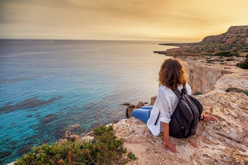 Printed kitchen splashbacks Cyprus A stylish young woman traveler watches a beautiful sunset on the rocks on the beach, Cyprus, Cape Greco, a popular destination for summer travel in Europe