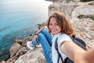 Beautiful young girl doing selfie on the background of a sea lagoon