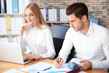 Young employees working with documents and laptop in office