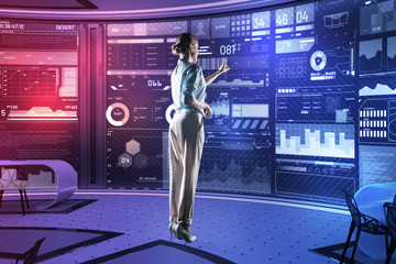 Young specialist. Smart experienced professional programmer standing in front of a transparent futuristic device and pointing to the screen of it while being in her equipped office