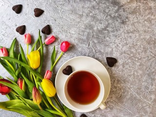 multi-colored tulips with a Cup of tea with cakes and chocolates