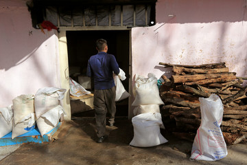 A worker carries sesame bags to be thrown in the stove at a sesame factory in Dohuk