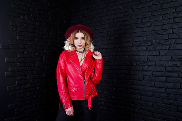 Studio portrait of blonde girl in red hat and leather jacket against brick wall.