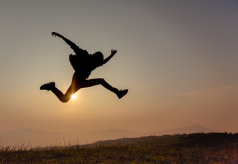 Silhouette of happy man jumping on Mountain