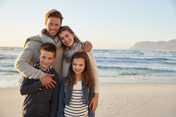 Portrait Of Family Walking Along Winter Beach Together