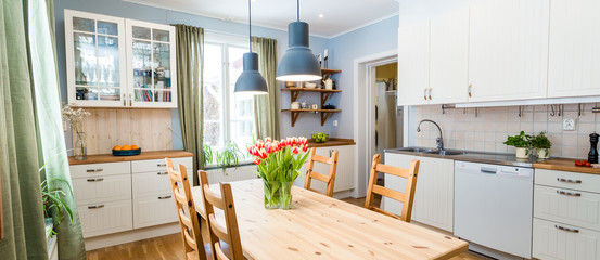 header of a kitchen with green curtains and table with orange taulips in a vase