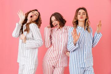 Portrait of three beautiful young girls 20s wearing colorful striped pyjamas having fun during...