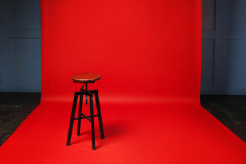Wooden retro stool on red background. No one, free space on the right.