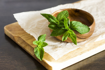 Leaves of fresh mint in a wooden bowl on the kitchen table