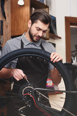 young worker in apron holding bicycle wheel and fixing chain in workshop