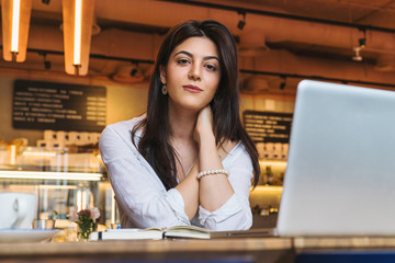 Portrait of young businesswoman, student, dressed in white blouse, sitting at table in cafe in front of computer.