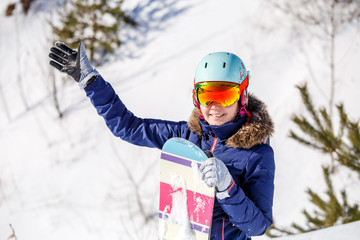 Portrait of smiling female athlete wearing helmet with snowboard