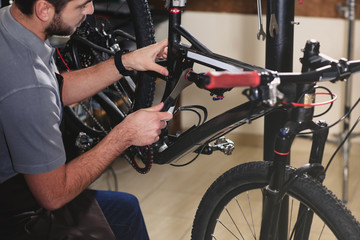 cropped shot of young worker fixing bicycle at workshop