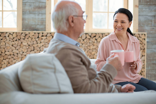 Hot tea. Joyful jolly caregiver gossiping with senior man while grinning and enjoying tea
