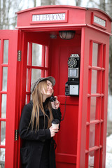 Beautiful young girl in a phone booth. The girl is talking on th