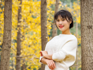 Young Chinese smiling girl portrait stand with golden autumn forest background in park. Outdoor.