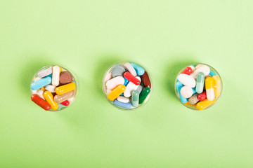 Three cups of colorful pills and tablets.