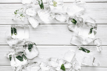 Flat lay of ice cubes with frozen aloe inside on white wooden table