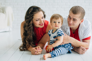 Happy family lying on the white floor. Parents having fun with daughter in dress. Woman with long dark curly hair in jeans and red blouse with white polka dots. White room