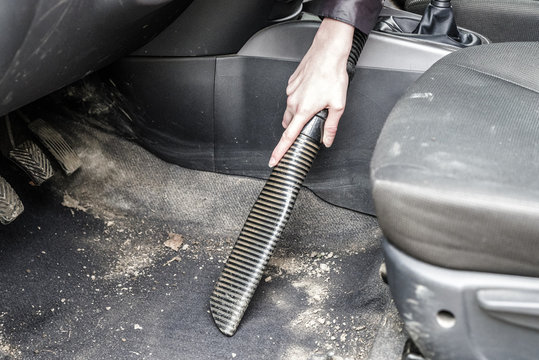Woman cleaning interior of car with vacuum cleaner