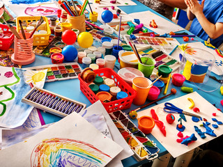Group hands keeps brush painting on table in kindergarten. Art workshop for talented child. Good hobby for children. Preparatory courses in drawing for schoolchildren.