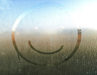 Kids draws of a smily face at a foggy glass