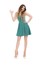 Beautiful Young Woman In Green Mini Dress And High Heels Is Showing Ok Hand Sign