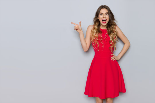 Happy Beautiful Woman In Red Dress Is Pointing And Shouting