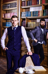 Men in suit, detectives spend leisure in library.